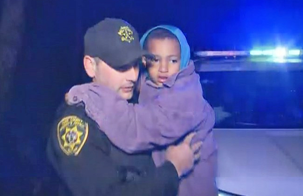 A member of the York County Sheriff's Office carries 5-year-old Christopher Grecco after the boy was found Monday morning lying down in the woods about a half-mile from where he was last seen.