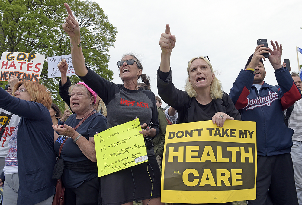 Protesters chant as Republican and Democratic House members walk down the steps of the Capitol  Thursday, after the Republican health care bill passed in the House.