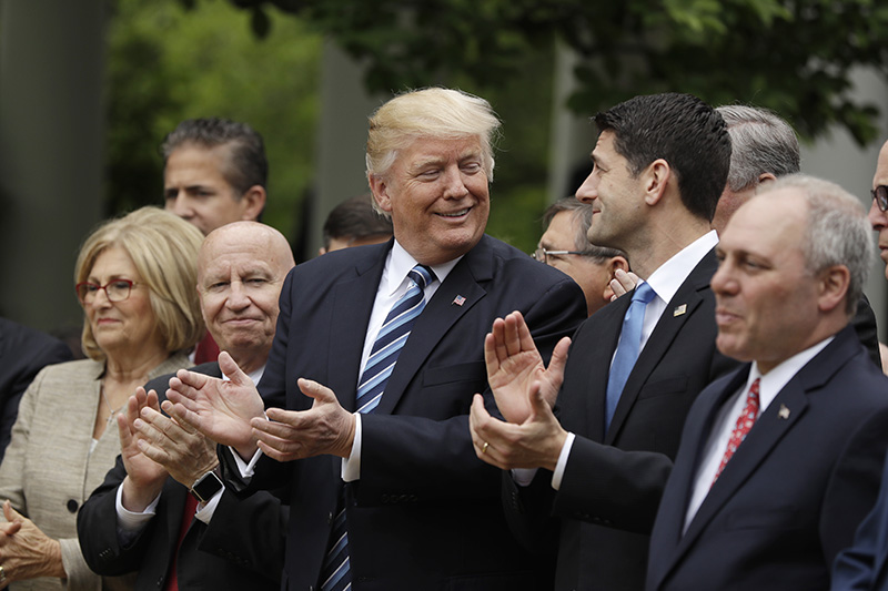 President Donald Trump, flanked by House Ways and Means Committee Chairman Rep. Kevin Brady, R-Texas, and House Speaker Paul Ryan of Wis. applaud in the Rose Garden of the White House after the passage of the health care bill.