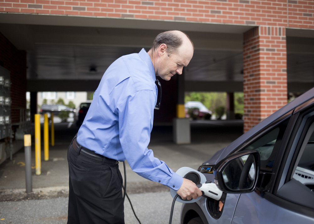 Barry Woods, 56, whose job with ReVision Energy of Portland is to promote electric cars, shows how to charge his Chevy Bolt, which he calls a game changer.