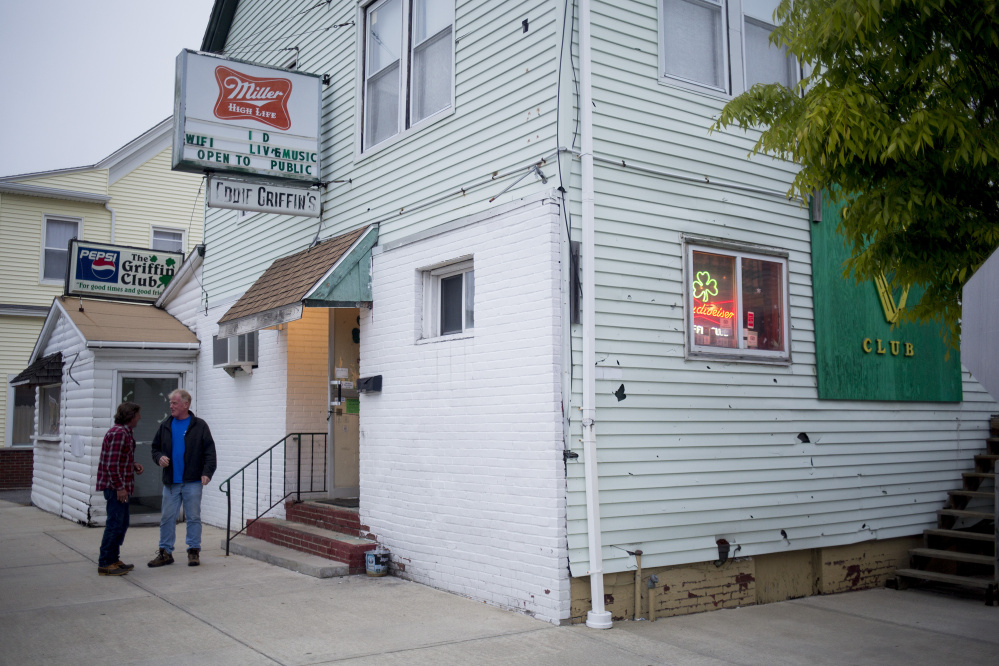Customers smoke last Wednesday outside the Griffin Club in South Portland during its last night of business. Penny Prior and Ginger Cote of Cape Elizabeth have bought the building.