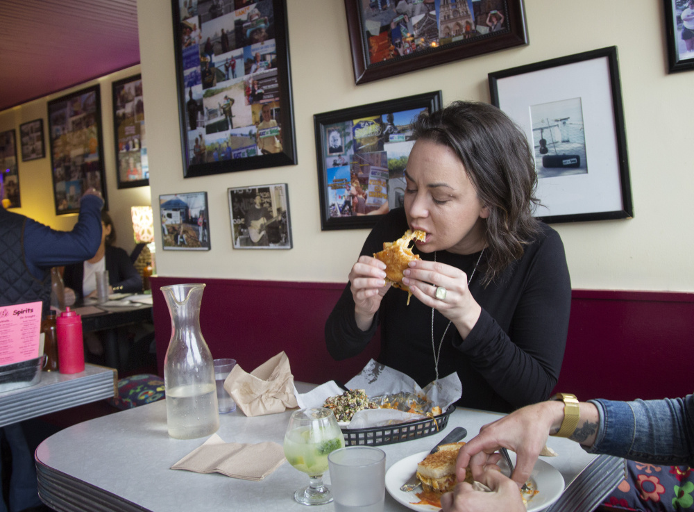 Vanessa Helmick feasts on a Vegan Meltaway, a vegan grilled cheese filled with tomatoes and caramelized onions at Silly's in Portland.