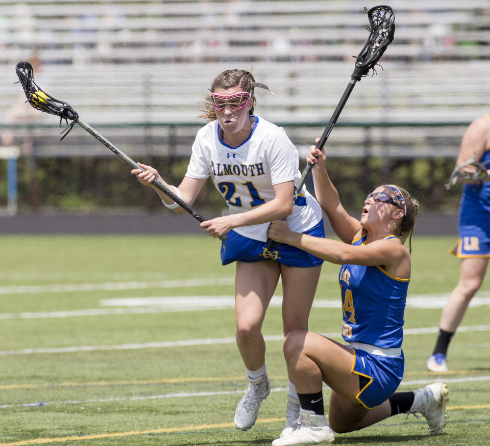 Lake Region's Olivia Deschenes, right, tries to keep her balance as she defends Falmouth's Sydney Bell during their Class B South semifinal Saturday in Falmouth. Bell collected two goals and two assists in Falmouth's 13-12 win.