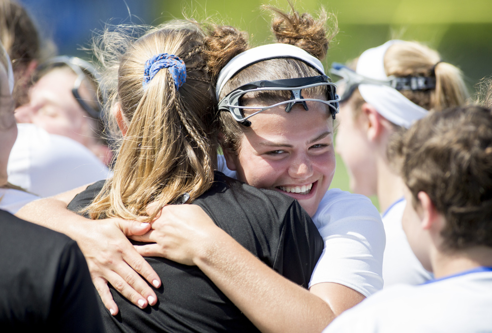Kayla Sarazin hugs a teammate after Falmouth earned a spot in the regional final Wednesday against top-seeded Kennebunk.