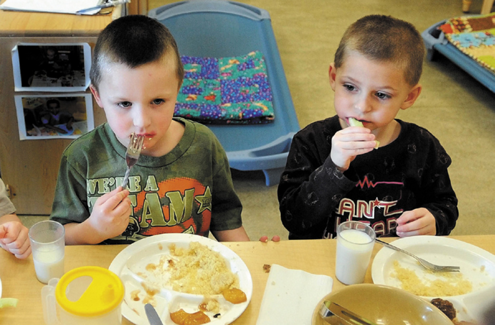 Justis Greene, 4, and Kayder Johnson, 5, eat lunch at Educare Central Maine in Waterville, in February 2013.