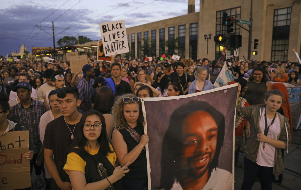 Marchers hold a portrait of Philandro Castile during a vigil Friday in St. Paul, Minn. The vigil follows police Officer Jeronimo Yanez being cleared of charges in the fatal shooting of Castile.
