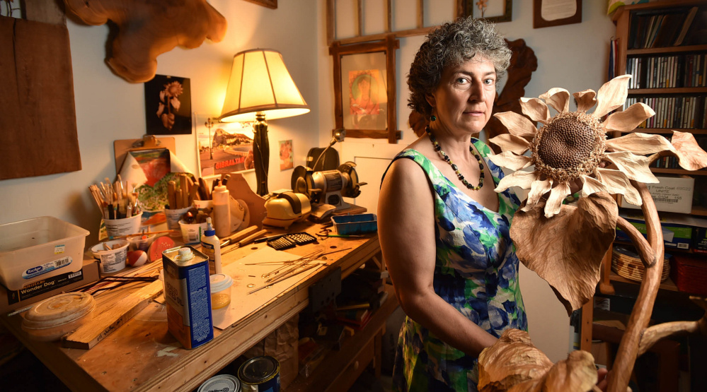 Canton artist Laurie Sproul with a wood sunflower in her home studio. Sproul and a Winslow-based artist are hoping their work helps lobbyists' effort to persuade Congress to act on climate change.