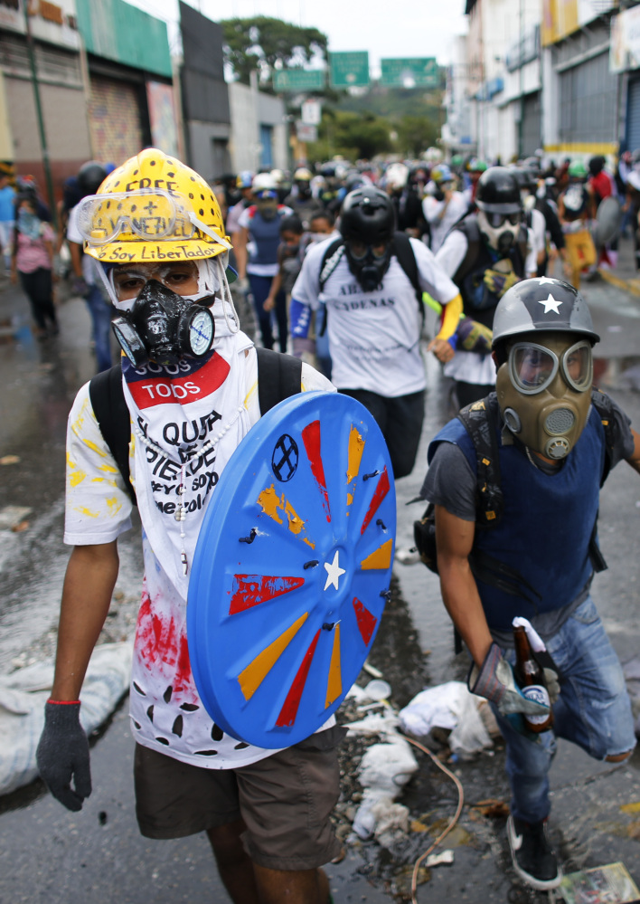 Anti-government demonstrators march in Caracas on Monday. Nearly 70 people have died in months of political unrest.