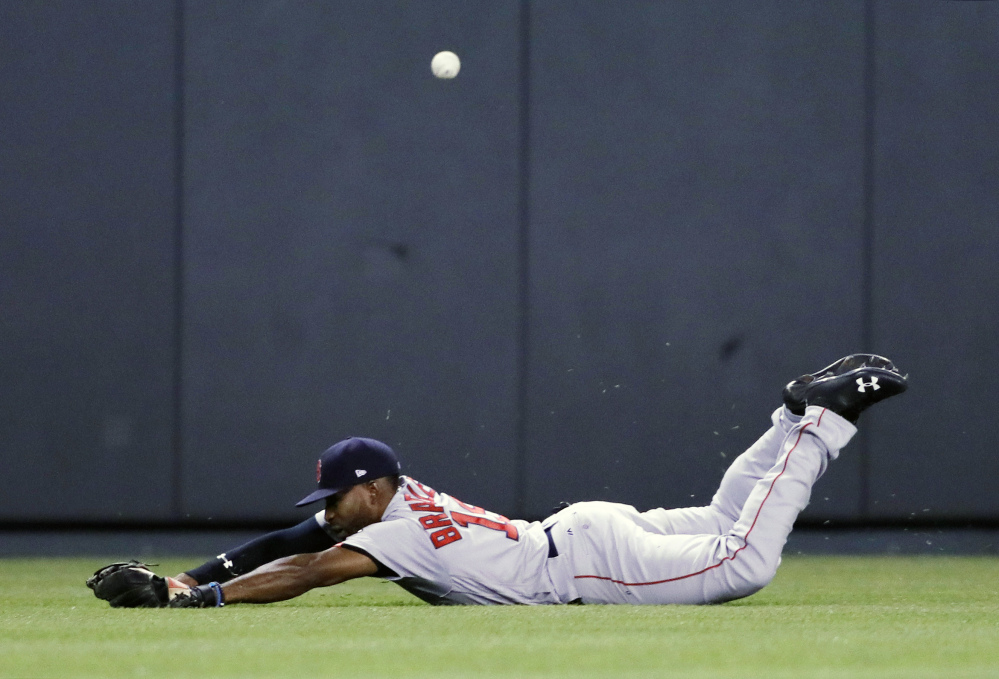 Red Sox center fielder Jackie Bradley Jr. dives but misses a fly ball by the Royals' Drew Butera, who got a triple on the seventh-inning play and later scored what proved to be the game-winning run.