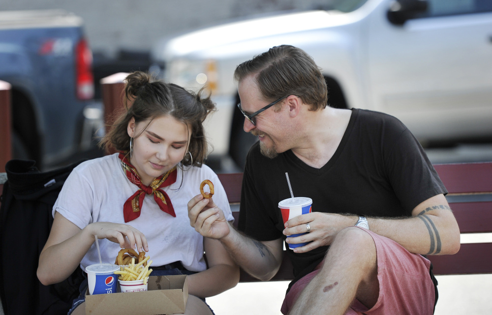 Joshua Bodwell, who first tasted fast food in the mid-1970s at Rapid Ray's in Saco, enjoys fries and onion rings there with his daughter Elona, 14, on Monday.