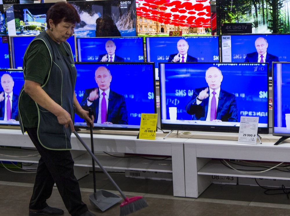 A worker passes TVs showing Russian President Vladimir Putin at his call-in show on Thursday in Moscow. Popular for his global role, his handling of corrupt officials is criticized.