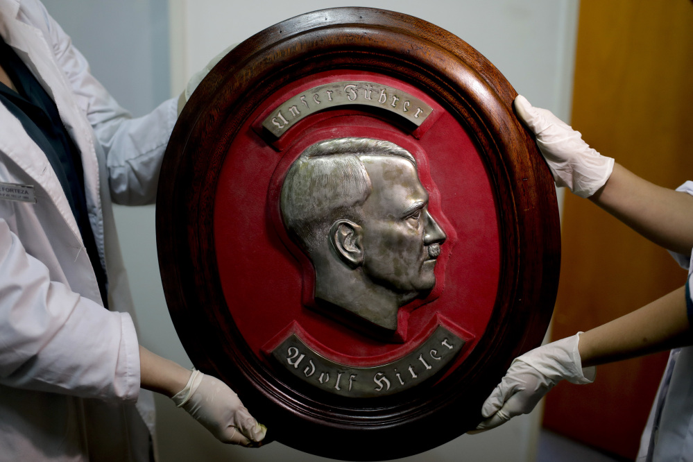 Members of the federal police show a bust relief portrait of Nazi leader Adolf Hitler at the Interpol headquarters in Buenos Aires, Argentina on Friday.