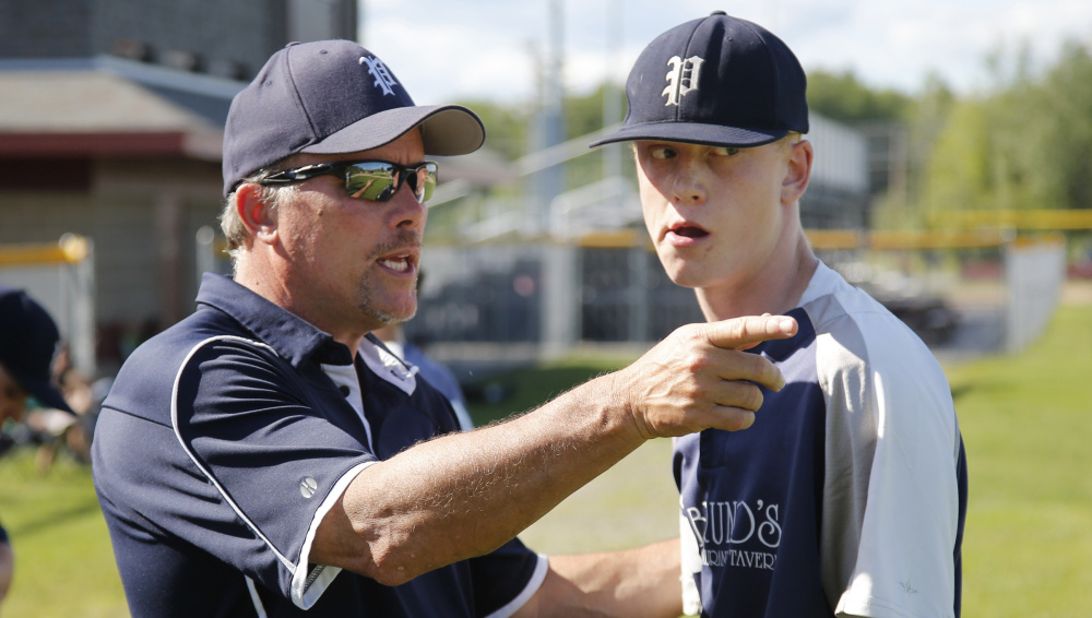 Portland Coach Mike Rutherford talks to his pitcher Jack Villani between innings of a game at Scarborough on Wednesday. The teams are among a group that has broken away from American Legion to form a new wooden-bat summer baseball league for high school players.