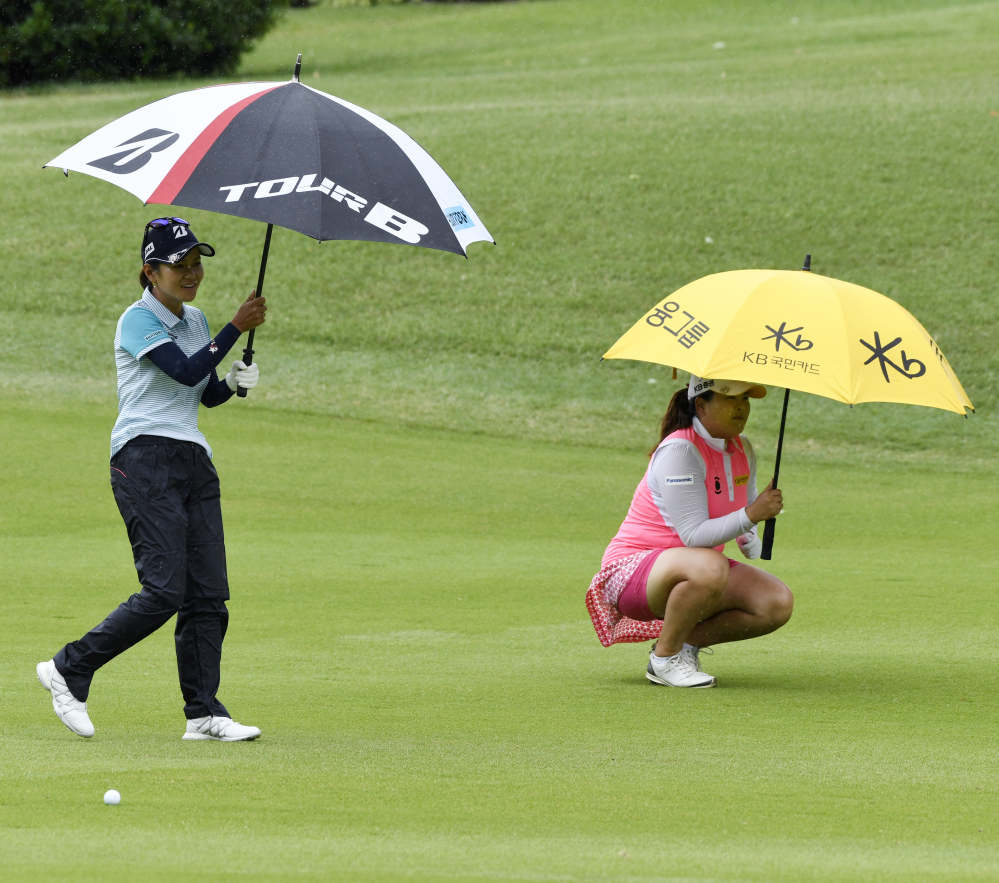 Ai Miyazato, left, of Japan, and Inbee Park, of South Korea, try to stay dry as it begins to rain while playing the second hole Friday during the LPGA Wal-Mart NW Arkansas Championship tournament at Pinnacle Country Club in Rogers, Ark.