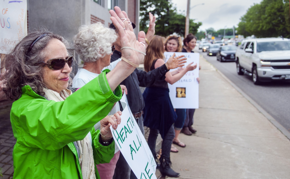 Leah Postman, left, of Winthrop waves to passing drivers after one of them honked during a health care demonstration Friday in front of the Edmund S. Muskie Federal Building on Western Avenue in Augusta.