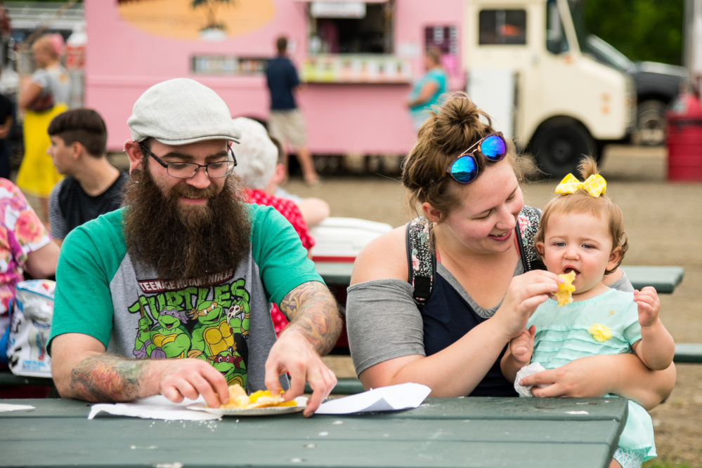 The Hamner family enjoys fried dough with lemon sauce Saturday during Kennebec River Day at Mill Park in Augusta. From left are Bryan, Loni and their daughter, 1-year-old Violet.