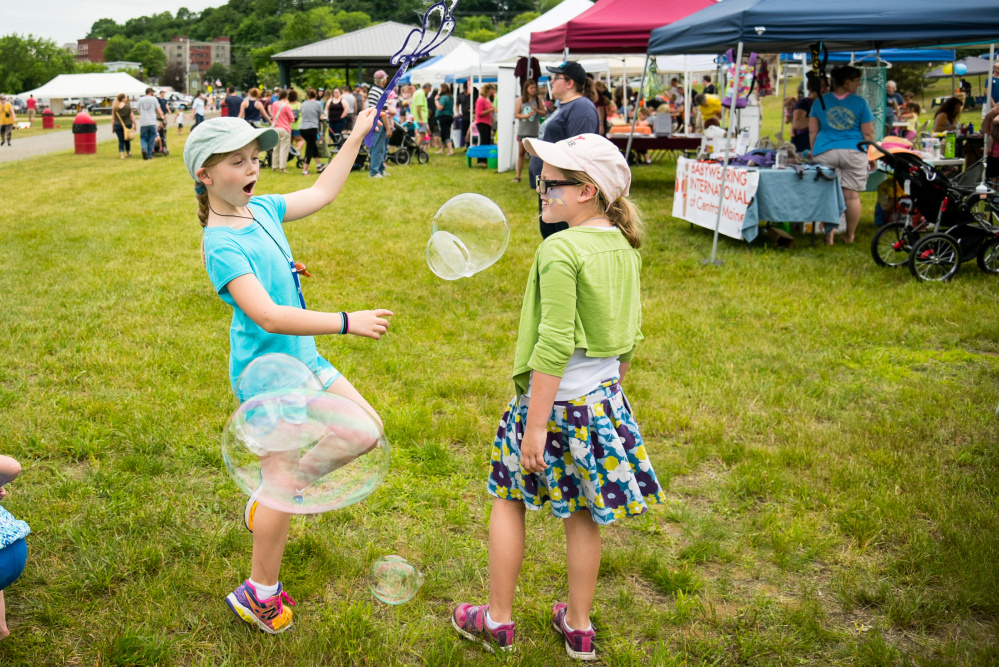 Alana, 8, left, and Sabine LaCourse, both of Boothbay, play with bubbles Saturday during Kennebec River Day at Mill Park in Augusta. The festival moved from Capitol Park to the river venue this year.