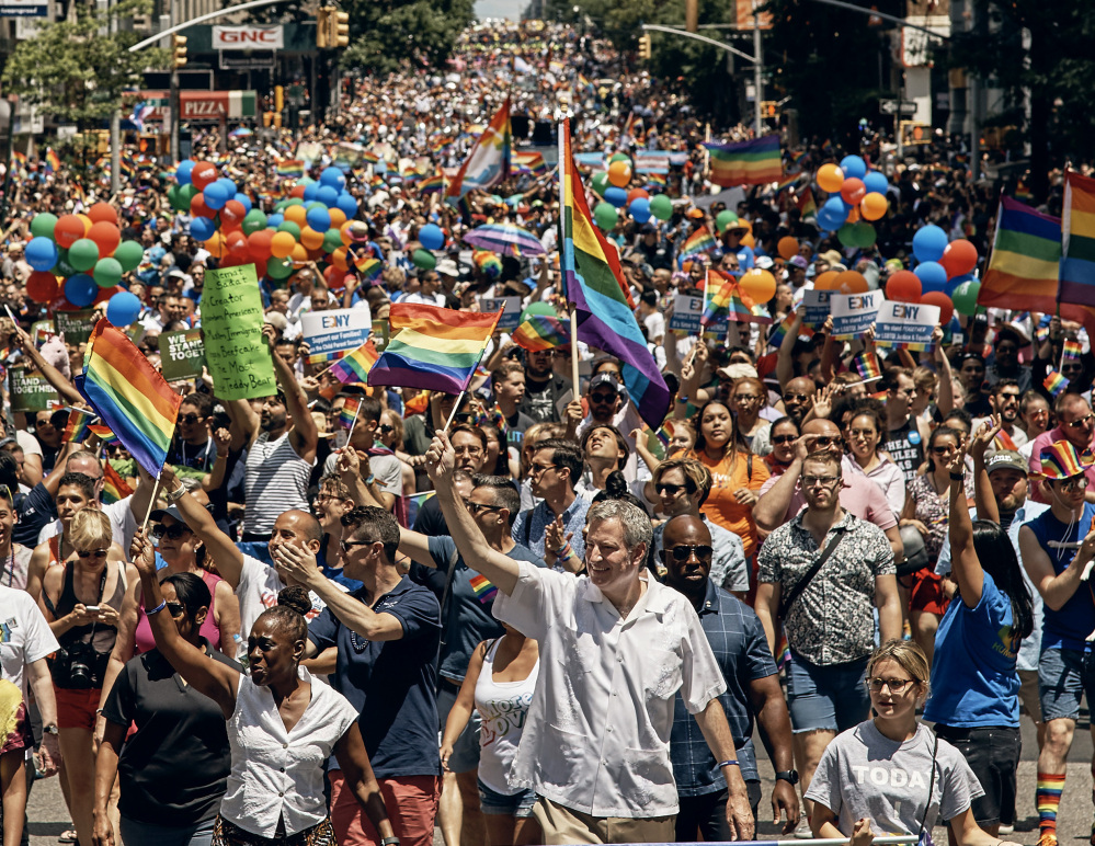 New York City Mayor Bill de Blasio, center, marches in the city's LGBT pride parade. Also Sunday, Gov. Andrew Cuomo appointed the first openly gay judge to the state Court of Appeals.