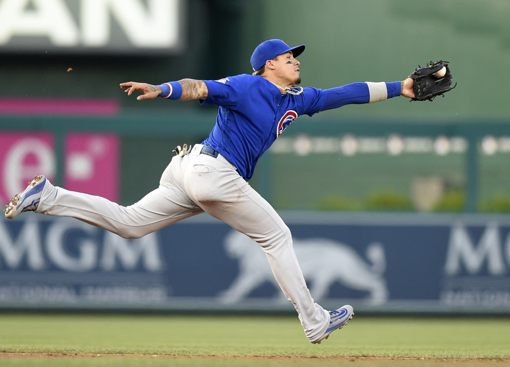 Cubs shortstop Javier Baez lunges for a ball hit by Trea Turner of the Nationals, but not in time to throw out Turner at first base. The Cubs survived Washington's four-run rally in the ninth, holding on for a 5-4 win.