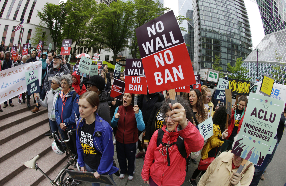 Protesters wave signs and chant during a May demonstration against President Trump's revised travel ban, outside a federal courthouse in Seattle. The Supreme Court is letting the Trump administration enforce its 90-day ban on travelers from six mostly Muslim countries, overturning lower court orders that blocked it.