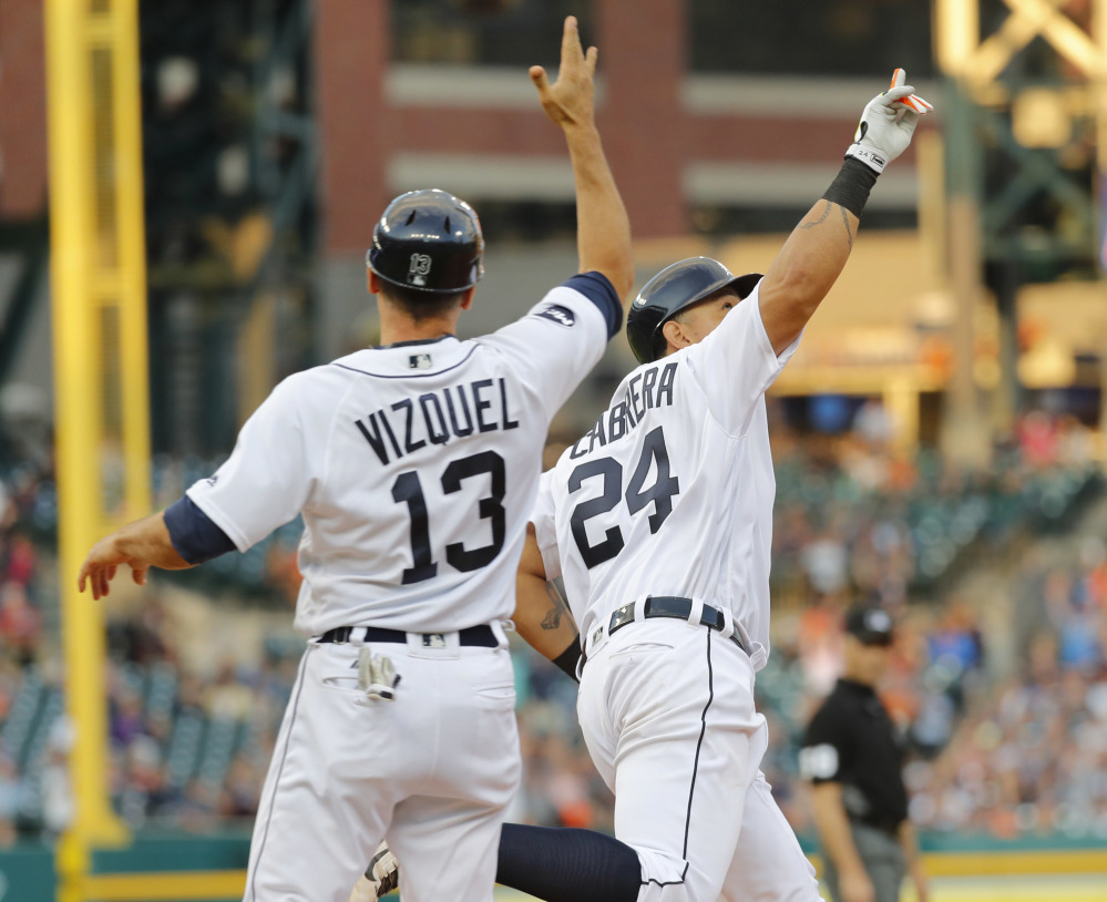 Miguel Cabrera of the Tigers, right, celebrates his three-run home run against the Royals with first-base coach Omar Vizquel during the third inning of Detroit's 5-3 win at home Tuesday.
