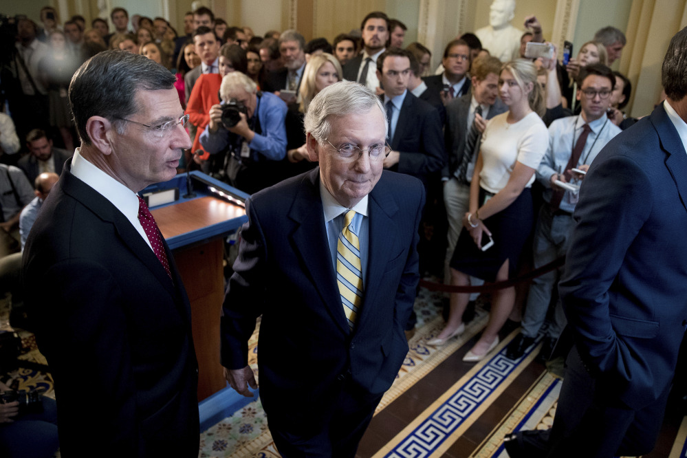 Senate Majority Leader Mitch McConnell, R-Ky., joined by Sen. John Barrasso, R-Wyo., left, shown after announcing that he was delaying a vote on the Republican health care bill on Tuesday, is aiming to revise the bill by Friday, aides say.