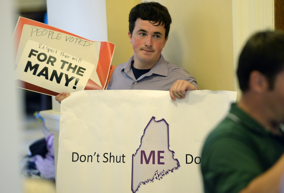 Nate LeClair of Auburn spreads his message opposing a government shutdown Tuesday at the State House. A closure would affect many of the state's more than 10,000 employees.