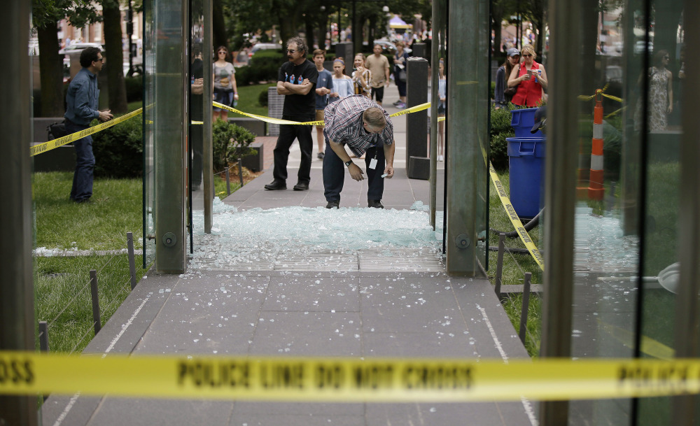 Spectators gather as Bob Satterlund, facilities manager for Combined Jewish Philanthropies of Boston, begins to pick up broken glass from one of the New England Holocaust Memorial's glass panels Wednesday.