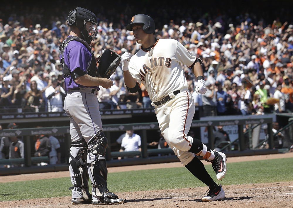 Giants rookie Jae-Gyun Hwang, called up before Wednesday's game to make his big league debut, crosses the plate after hitting a go-ahead homer in the sixth inning against Colorado.