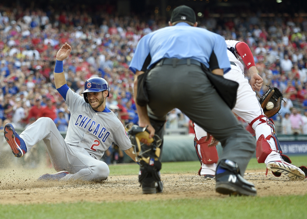 Tommy La Stella of the Chicago Cubs slides home to score on Jon Jay's two-run double in the ninth inning of the 5-4 comeback victory Thursday against the Washington Nationals.