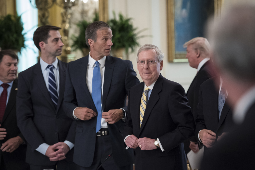 From left, Sens. Tom Cotton, R-Ark., John Thune, R-S.D., and Mitch McConnell, R-Ky., stand as President Trump arrives for a meeting with Republican senators about health care at the White House on Tuesday.