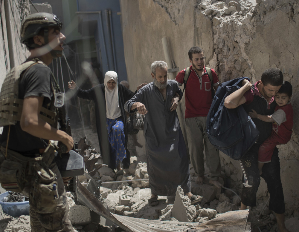 Iraqi civilians flee through a destroyed alley as Iraqi Special Forces move toward Islamic State positions in the Old City of Mosul on Friday.