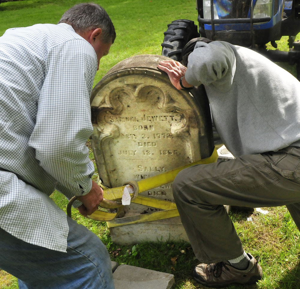 It took a few tries to align the stone on the grave pedestal as Hank McIntyre, left, and Logan Johnston strap the heavy stone.