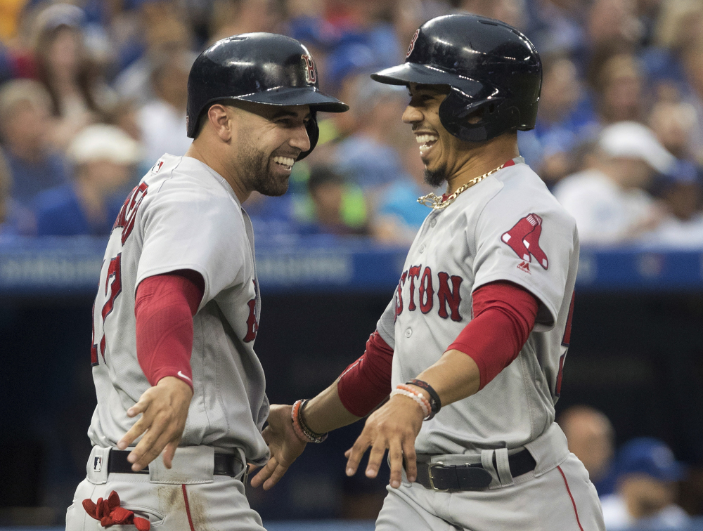 Boston's Mookie Betts, right, celebrates with Deven Marrero after scoring on a Dustin Pedroia double in the fifth inning Friday night against the Blue Jays at Toronto.