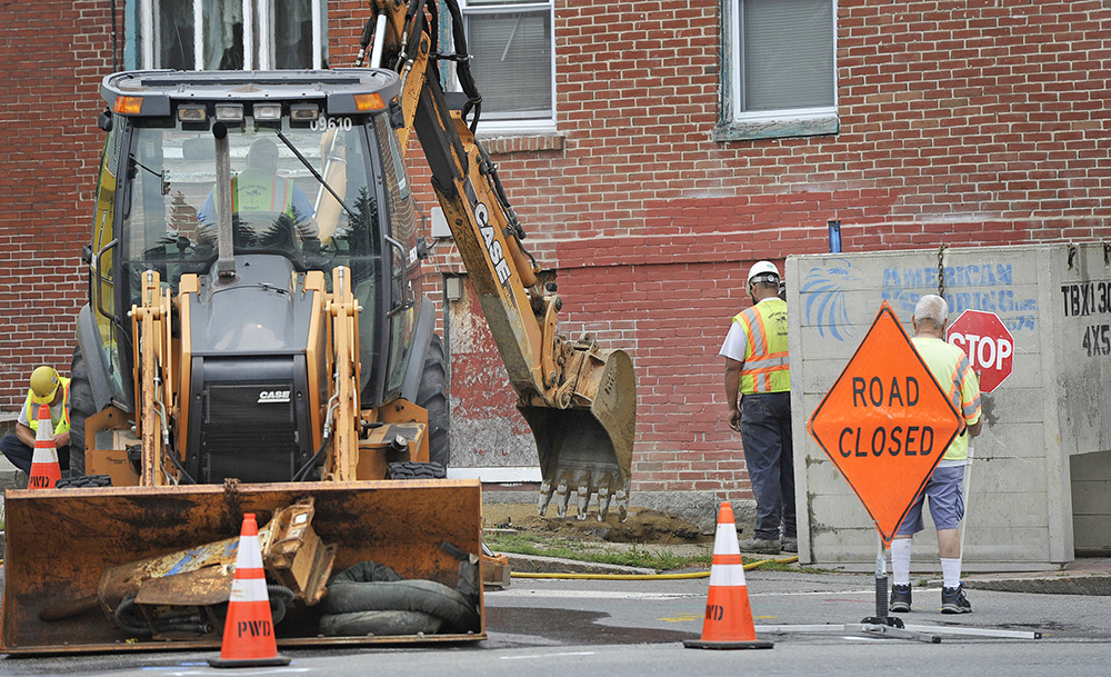 Crews work to restore a water main break at the corner of State and York streets in Portland Friday.