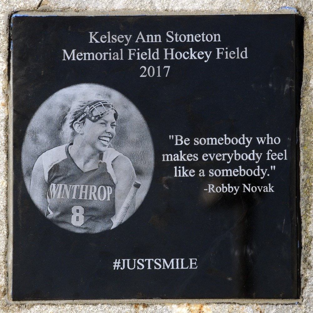 ... and Joel Stoneton look at a plaque honoring their late daughter Kelsey Ann Stoneton on Wednesday at the field hockey field at Winthrop High School.