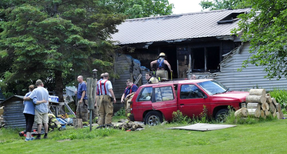 Firefighters from several area departments battled a fire that destroyed a home Thursday on Higgins road in Pittsfield. Homeowner Tyler Bishop, second from left, is comforted by a woman.