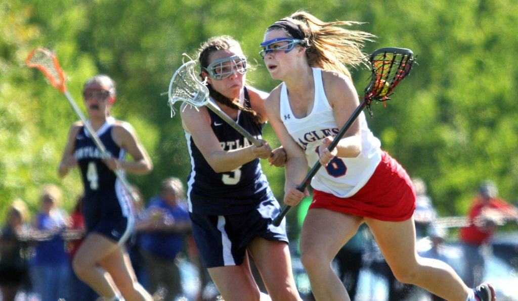Messalonskee's Lauren Pickett moves the ball up field past Portland's Elena Clifford during the first half a Class A girls' lacrosse quarterfinal Wednesday at Thomas College in Waterville.