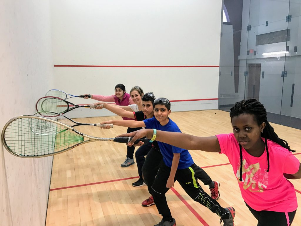 At Portland Community Squash on Noyes Street, coach Marilu Fortson, second from left, works with students, from left, Fatima Al-Bayati, Ahmed Albadri, Yousif Ali, and Auxane Bahunde Iriza.