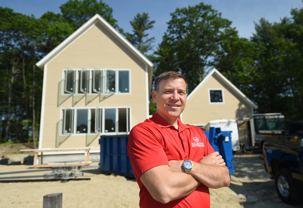 Builder Matt Brewer in front a a custom energy-efficient home in Village Run, a new subdivision in Yarmouth originally envisioned as a neighborhood of modular, high-performance homes.