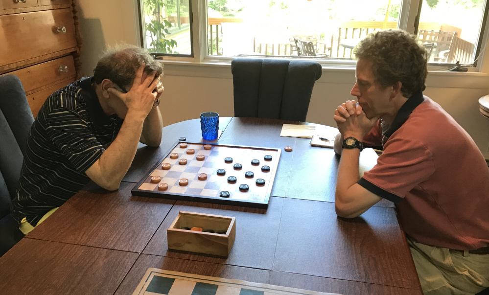 Six-time defending New England checkers champion Joseph Margolin holds his head in concentration against tournament newcomer Glenn Jordan.