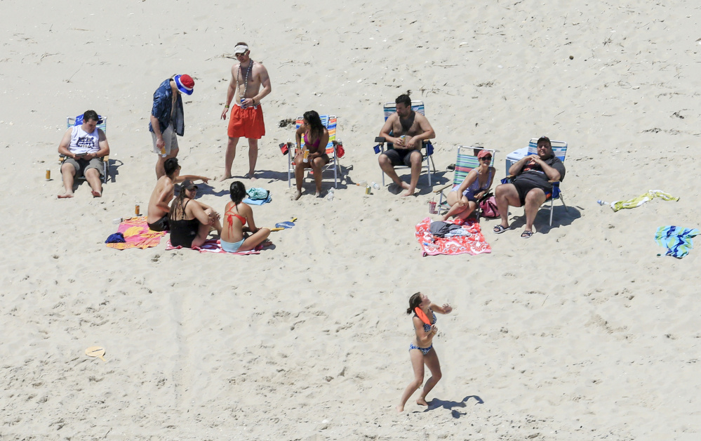 New Jersey Gov. Chris Christie, right, uses the beach with his family and friends at the governor's summer house at Island Beach State Park on Sunday. Christie is defending his use of the beach, which was closed to the public.