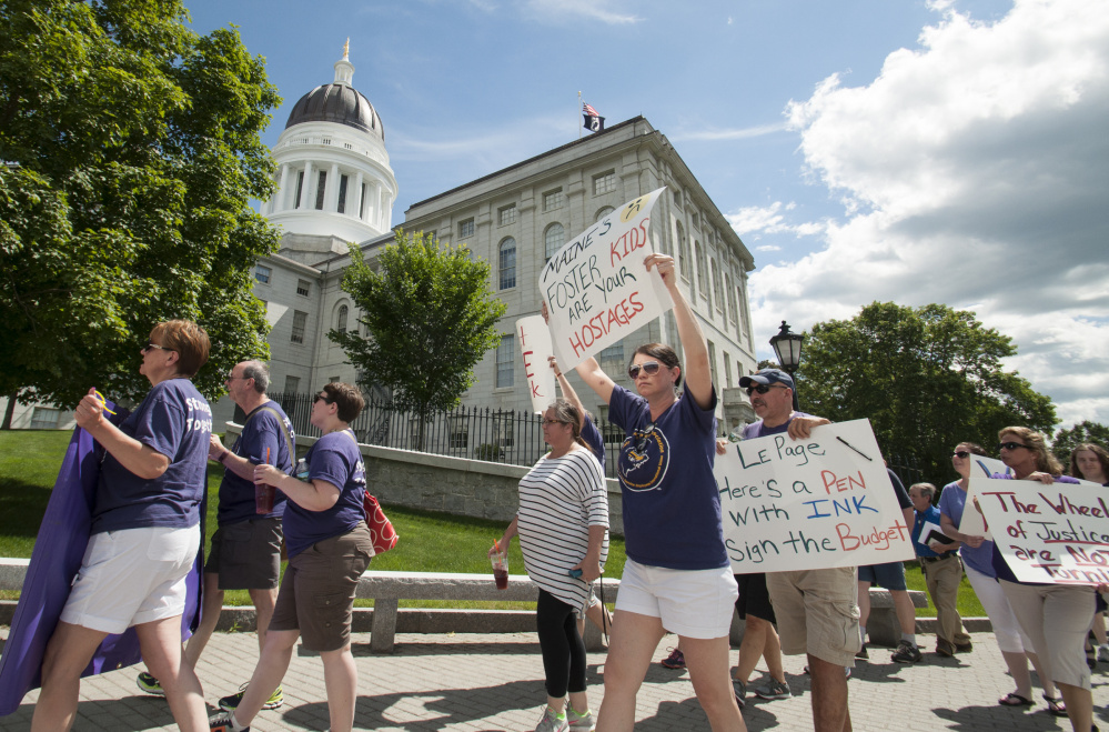State workers and supporters march past the State House on Monday, urging legislators to break a budget impasse.