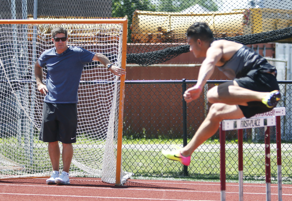 Former Kennebunk High track star Jamie Cook watches as Devon Allen works out Monday at Thornton Academy in Saco. Cook, a former assistant coach at the University of Oregon, brought Allen and Johnathan Cabral to Maine for a workout in front of high school athletes and coaches.