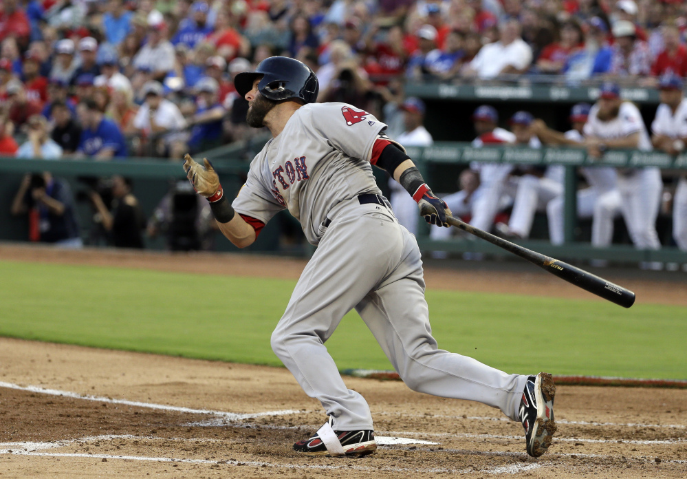 Dustin Pedroia hits a two-run single in the second inning Monday night against the Texas Rangers. Pedroia drove in four runs in the game.