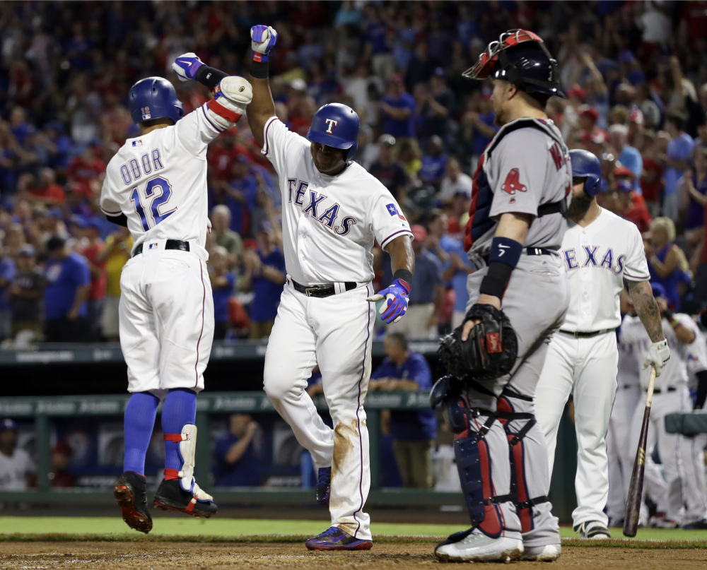 The Rangers' Rougned Odor (12) and Adrian Beltre celebrate Odor's two-run home run that scored Beltre in the second inning of what became a romp for the Rangers.