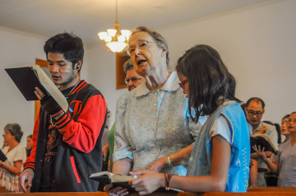 Miriam Charles, center, prays beside Paday Shee, left, and Paw Shee at Habecker Mennonite Church in Lancaster, Pa. Paday, 25, and Paw, 10, are not related but are part of the group of ethnic Karen refugees from South Asia who attend the church.