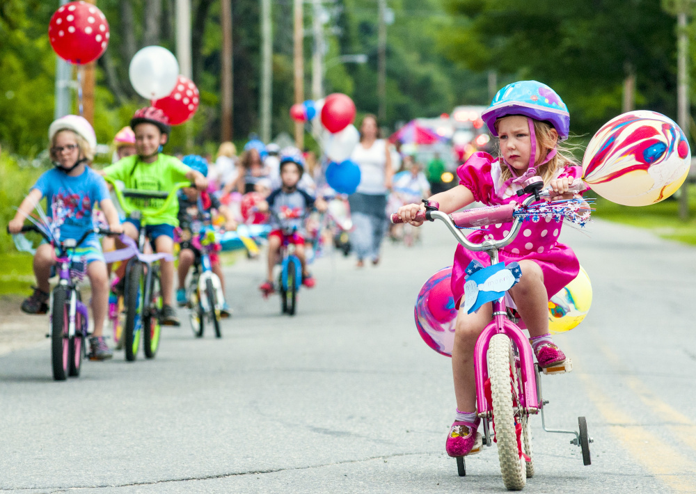Alice Lazure, 4, seems to concentrate hard as she rides her bike in the town's parade on Saturday in Monmouth.