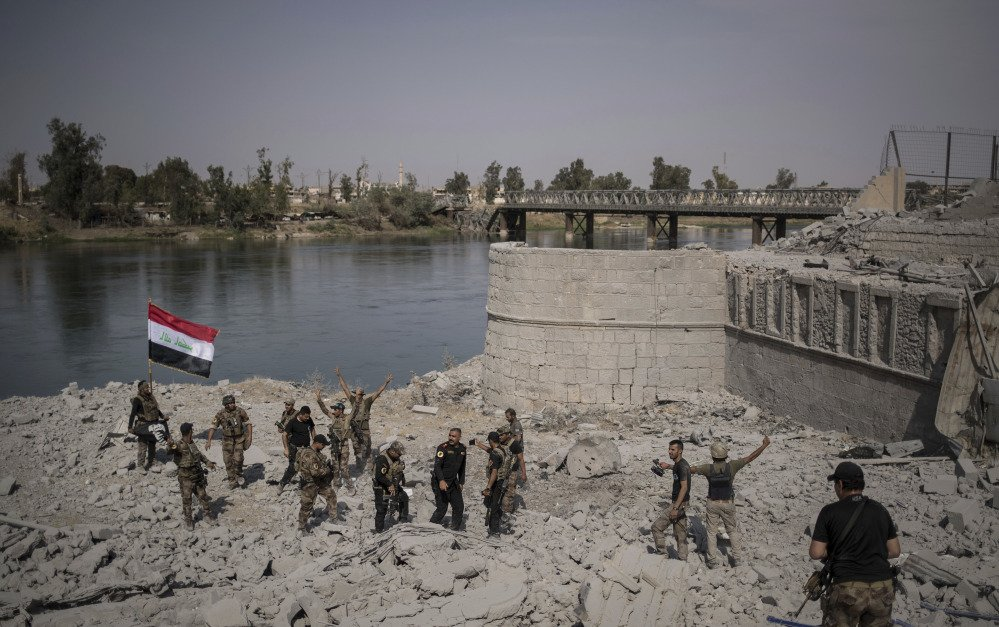 Iraqi soldiers celebrate after reaching the bank of the Tigris River in their fight against Islamic State militants in Mosul.