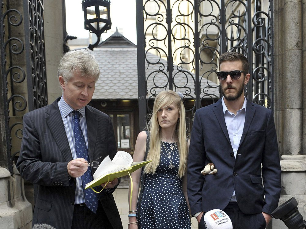 The parents of sick baby Charlie Gard, Connie Yates and Chris Gard, right, listen as a statement is read by a family friend outside the High Court in London on Monday.